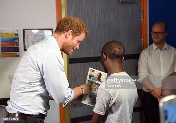 Prince Harry looks at photos with 16 yearold Relebohile 'Mutsu' Potsane after watching members of the Basotho Youth Choir during their rehearsals at...