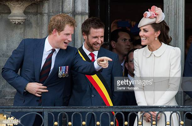 Prince Harry makes a joke as Catherine Duchess of Cambridge looks on from the balcony of the town hall as they attend a reception at the Grand Place...