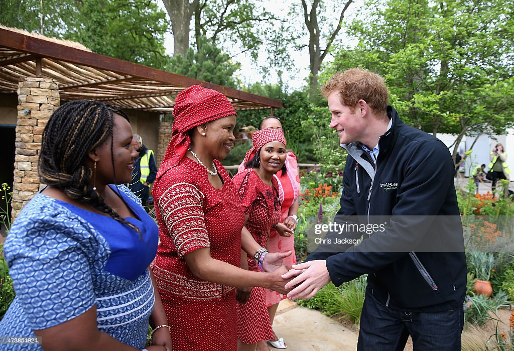 Prince Harry meets Basotho singers from Lesotho as he visits the Sentebale 'Hope In Vunerability' Garden during the annual Chelsea Flower show at Royal Hospital Chelsea on May 18, 2015 in London, England.