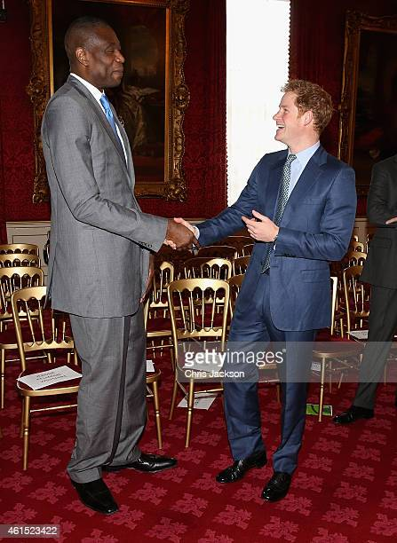 Prince Harry meets NBA global ambassador Dikembe Mutombo during a Coach Core Graduation event at St James's Palace on January 14 2015 in London...