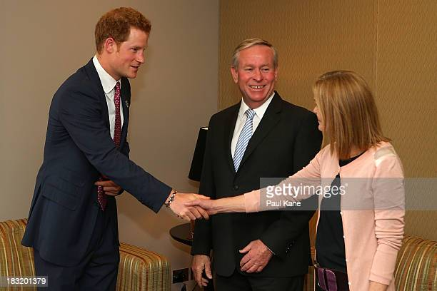 Prince Harry meets with West Australian Premier Colin Barnett and his wife Lyn Barnett after arriving at Perth Airport on October 6 2013 in Perth...