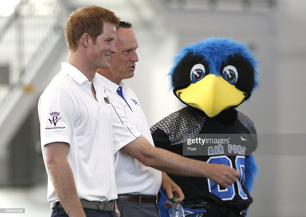 HRH Prince Harry observes a football demonstration with United States Air Force Academy head football coach Troy Calhoun (C) and mascot, 'The Bird' at the United States Air Force Academy's football training center during the fourth day of his visit to the United States on May 12, 2013 in Colorado Springs, Colorado. HRH will be undertaking engagements on behalf of charities with which the Prince is closely associated on behalf also of HM Government, with a central theme of supporting injured service personnel from the UK and US forces.