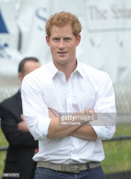 Prince Harry of Wales looks on at kids playing baseball during the fifth day of his visit to the United States at Harlem RBI on May 14 2013 in New...