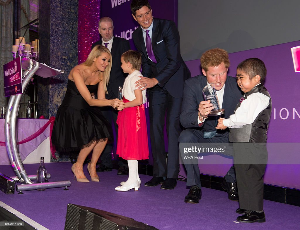 <a gi-track='captionPersonalityLinkClicked' href=/galleries/search?phrase=Prince+Harry&family=editorial&specificpeople=178173 ng-click='$event.stopPropagation()'>Prince Harry</a>, Patron of WellChild (2nd R) presents an award to Jonathan He, age 6, from Milton Keynes, and Tess Daley presents an award to Maidison Kirk, age 6, with an award, watched by <a gi-track='captionPersonalityLinkClicked' href=/galleries/search?phrase=Vernon+Kay&family=editorial&specificpeople=211386 ng-click='$event.stopPropagation()'>Vernon Kay</a>, on stage during the 8th annual WellChild Awards at Dorchester Hotel, Park Lane on September 11, 2013 in London, England. Jonathan He won the 'Most Inspirational Child' award for boys aged three to six years old, for his bravery in battling a life-threatening illness. Madison Kirk, from Grantham, who has undergone surgery and months of chemotherapy treatment for anaplastic large cell lymphoma, won an award in the 'Inspirational Child' category. The WellChild national charitable organisation cares for the individual needs of children coping with consequences of serious illness and complex medical conditions.