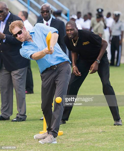 Prince Harry plays cricket as Sir Curtly Ambrose looks on during a Youth Sports Festival at the Sir Vivian Richards Stadium on the second day of an...