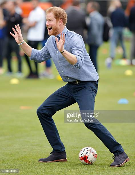 Prince Harry plays football as he attends an event to mark the expansion of the Coach Core sports coaching apprenticeship programme at Lord's cricket...