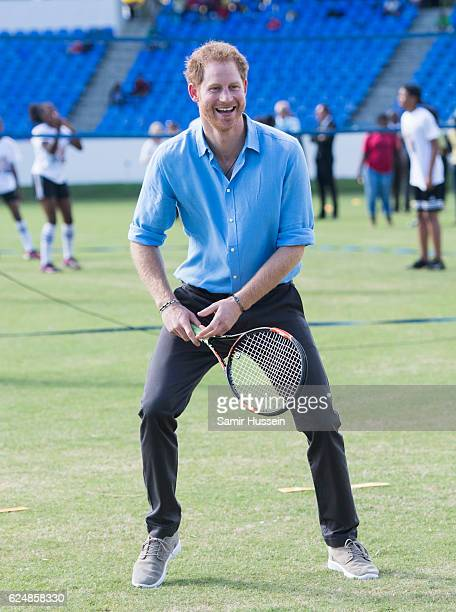 Prince Harry plays tennis during a Youth Sports Festival at the Sir Vivian Richards Stadium on the second day of an official visit on November 21...