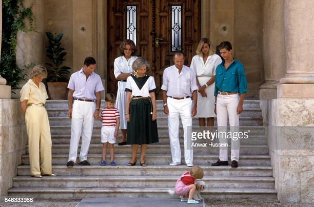 Prince Harry plays with a dog watched by Prince William Prince Charles Prince of Wales and Princess Diana Princess of Wales and the Spanish Royal...