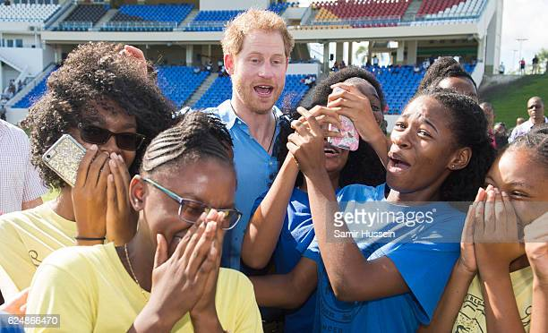 Prince Harry poses with a group of girls at a Youth Sports Festival at the Sir Vivian Richards Stadium on the second day of an official visit on...
