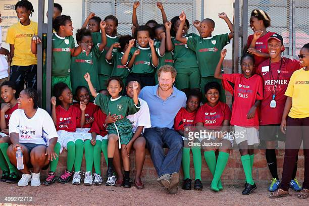 Prince Harry poses with children during a visit to a Football for Hope session with Grassroots Soccer in Khayelitsha on November 30 2015 in Cape Town...