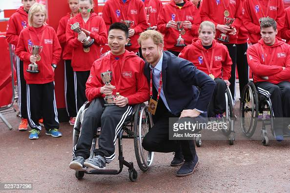 Prince Harry poses with junior 5K runners during the Virgin Money Giving London Marathon at the finish on The Mall on April 24 2016 in London England