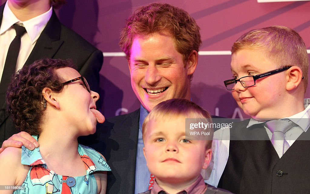 Prince Harry poses with (L-R) Rose Whittle, 9, Alex Logan, 6, and Matthew Merritt, 9, at the WellChild Awards at the Intercontinental Hotel on September 3, 2012 in London, England.