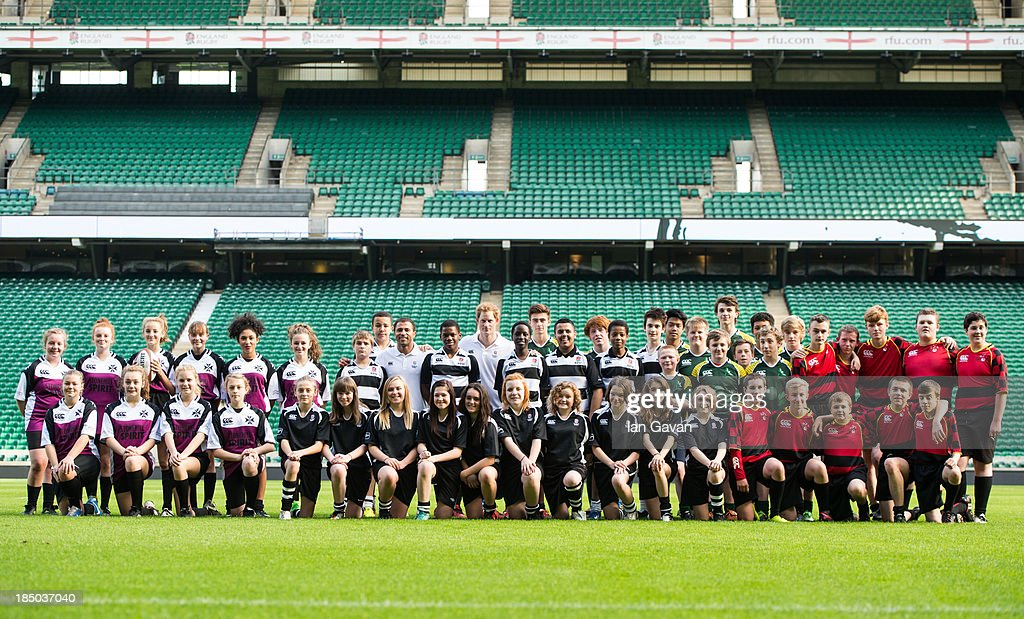Prince Harry poses with the teams on the pitch during the RFU All School programme coaching event at Twickenham Stadium on October 17, 2013 in London, England.