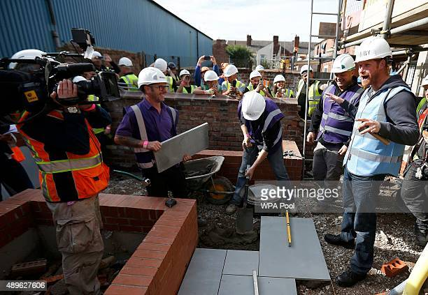 Prince Harry prepares to lay some paving slabs as he helps to renovate homes for exservice personnel as part of the BBC television DIY SOS series on...
