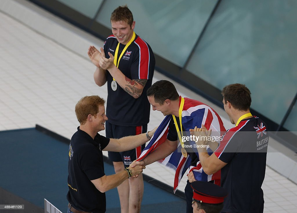 Prince Harry presents medals to competitors at the Invictus Games swimming at the London Aquatics Centre at Olympic Park on September 14, 2014 in London, England. Photo: