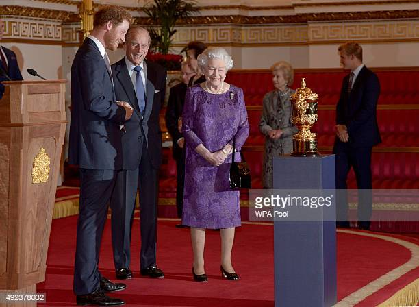 Prince Harry Prince Philip Duke of Edinburgh and Queen Elizabeth II look at the Webb Ellis Cup on a plinth during a Rugby World Cup reception at...