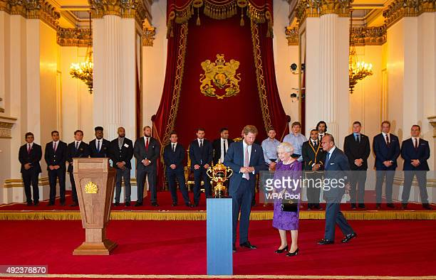 Prince Harry Queen Elizabeth II and Prince Philip Duke of Edinburgh view the Webb Ellis Trophy at a Rugby World Cup reception at Buckingham Palace on...