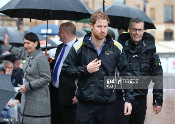 Prince Harry reacts as he walks away after meeting members of the public in the pouring rain at The Rocks on June 7 2017 in Sydney Australia Prince...