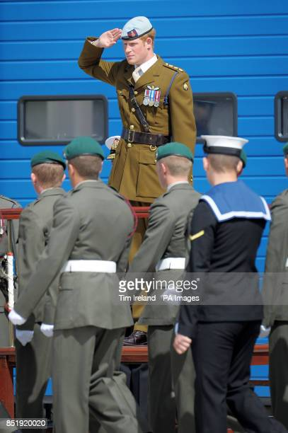 Prince Harry salutes as members of 1 Assault Group Royal Marines parade past a plaque he unveiled during a visit to the Royal Marines Tamar centre at...