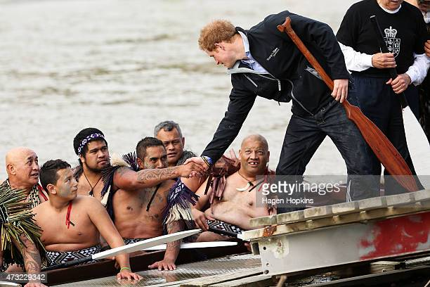 Prince Harry shakes hands with a member of the crew after paddling a waka on the Whanganui River during a visit to Putiki Marae on May 14 2015 in...