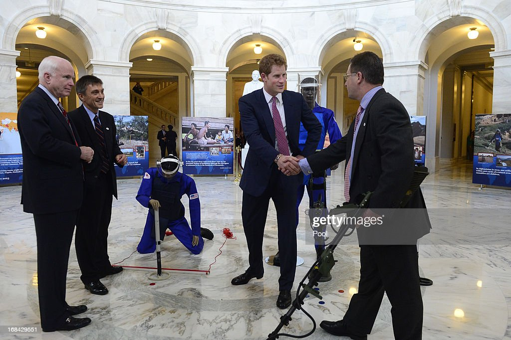 Prince Harry (R) shakes hands with HALO Trust Weapons and Ammunition Disposal Desk Officer Richard Boulter (R), while being shown equipment used for detecting land mines during a tour of a HALO Trust photo exhibit on landmines and unexploded ordinances, with Republican Senator from Arizona John McCain (L) and HALO Trust Afghanistan Desk Officer Tim Porter (2-L), on Capitol Hill on May 9, 2013 in Washington, DC. HRH will be undertaking engagements on behalf of charities with which the Prince is closely associated on behalf also of HM Government, with a central theme of supporting injured service personnel from the UK and US forces.