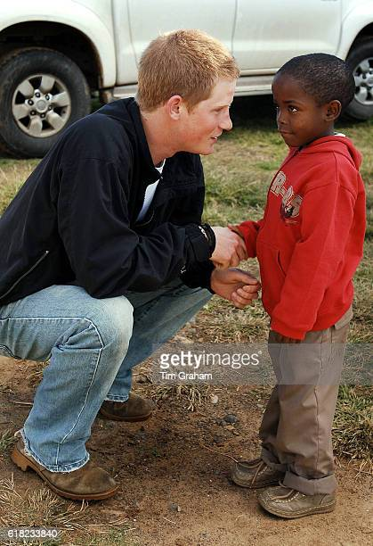 APRIL 28 2006*** Prince Harry shakes hands with his friend Mutsu Potsane in the grounds of the Mants'ase children's home while on a return visit to...