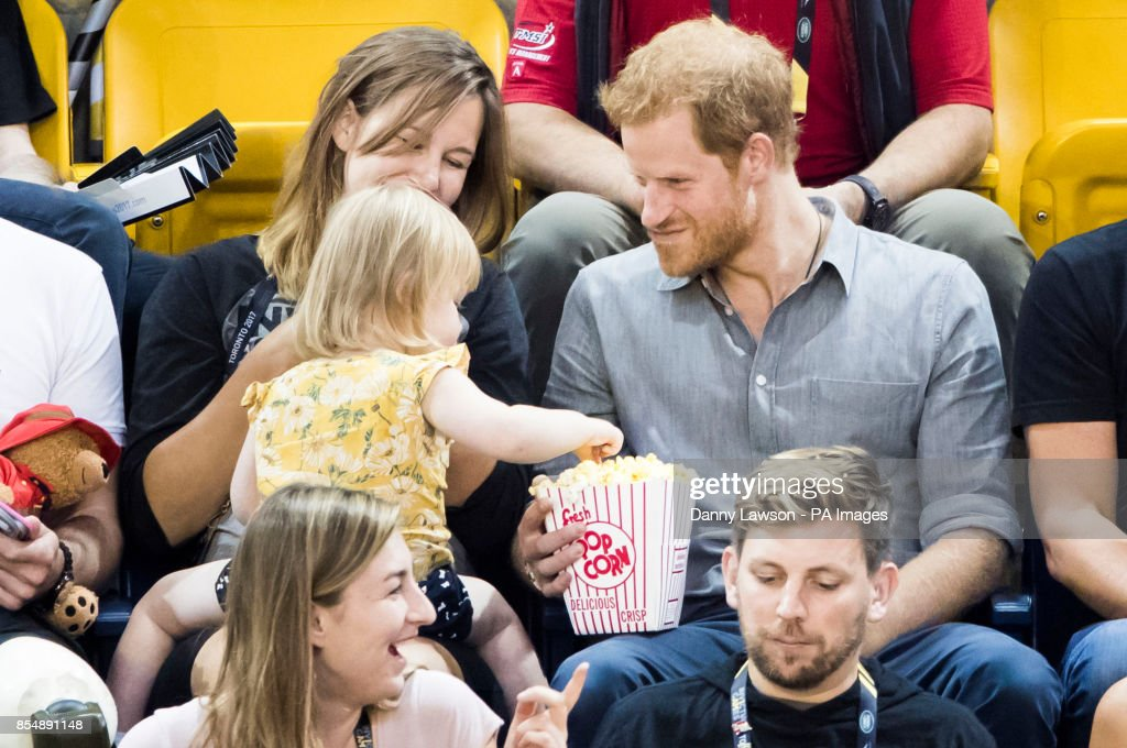 Prince Harry shares his pop corn with Emily Henson, daughter of Hayley Henson (left) as he attends the Sitting Volleyball Finals at Mattamy Athletic Centre during the 2017 Invictus Games in Toronto, Canada.