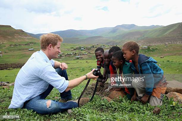 Prince Harry shows children a photograph he has taken on a Fuji X100s Camera during a visit to a herd boy night school constructed by Sentebale on...