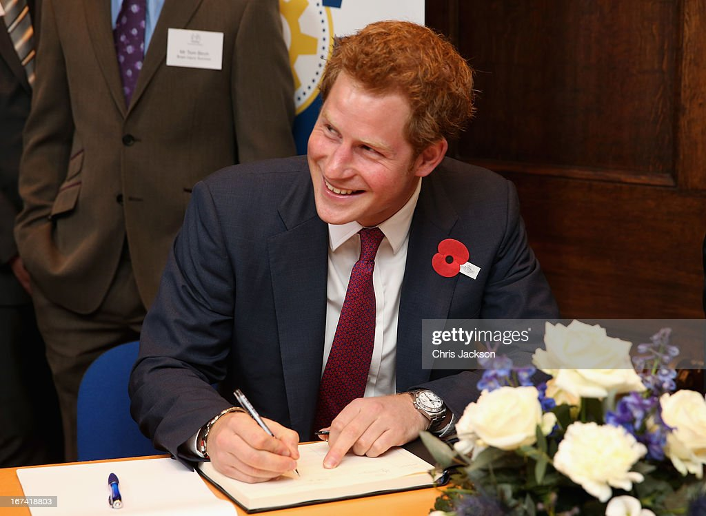 Prince Harry signs a visitors book during his visit to Headway, the brain injury association at Bradbury House during an official visit to Nottingham on April 25, 2013 in Nottingham, England.