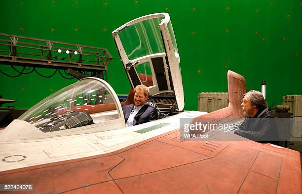 Prince Harry sits in an Awing fighter as he talks with US actor Mark Hamill during a tour of the Star Wars sets at Pinewood studios on April 19 2016...