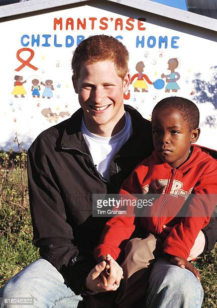 APRIL 28 2006*** Prince Harry sits with his old friend Mutsu Potsane in the grounds of the Mants'ase children's home while on a return visit to...