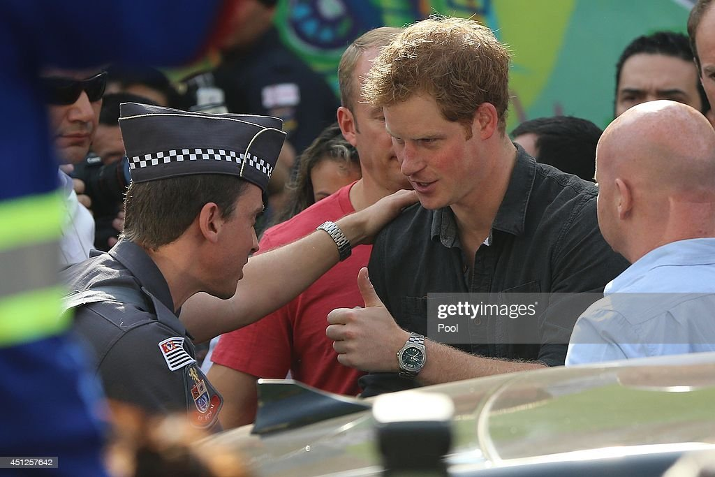Prince Harry speaks to a policeman as he visits the Open Arms project which helps reduce crime and drug abuse in 'Cracolandia', an extremely deprived area of Sao Paulo with a high concentration of crack addicts on June 26, 2014 in Sao Paulo Brazil. Crack in Sao Paulo costs just 80 UK pence for a rock of the drug. Prince Harry is on a four day tour of Brazil that will be followed by two days in Chile.