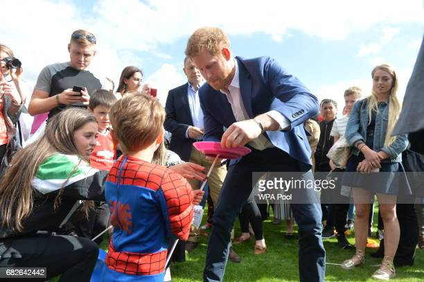 Prince Harry speaks to children as he along with Prince William Duke of Cambridge and Catherine Duchess of Cambridge host Party at The Palace they...