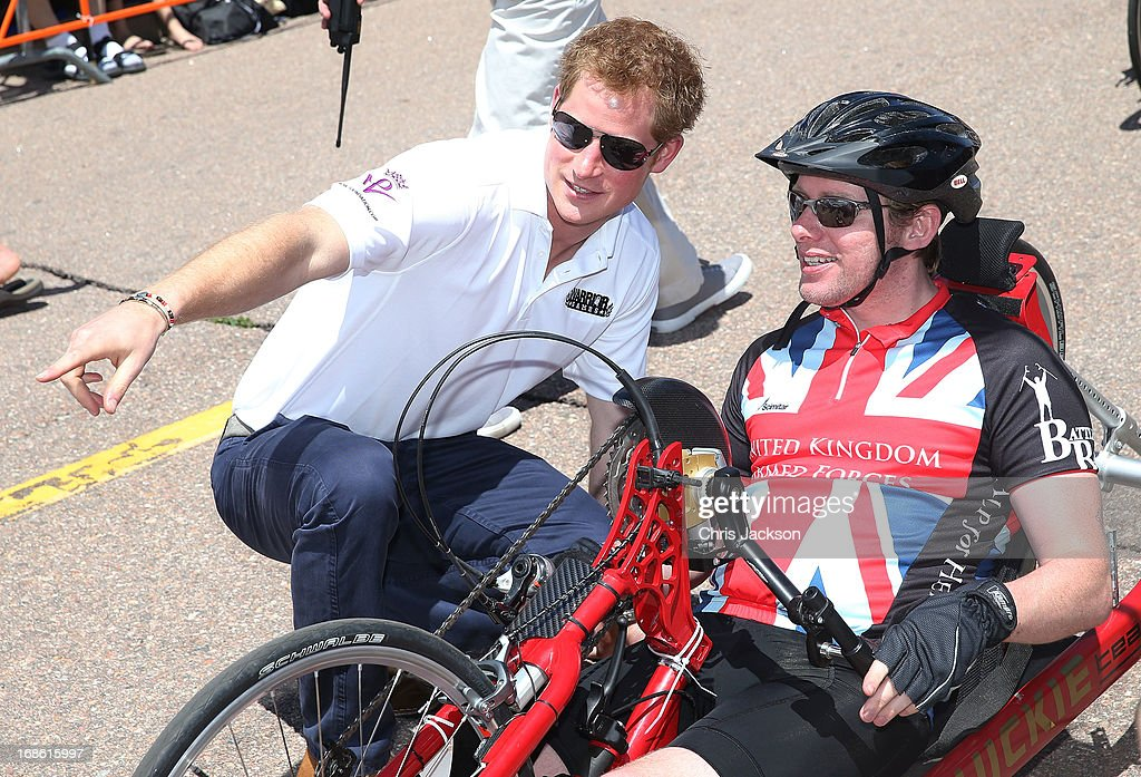 Prince Harry speaks to competitors as he attends the US airforce training academy hand cycling event at the Warrior Games during the fourth day of his visit to the United States on May 12, 2013 in Colorado Springs, Colorado. HRH will be undertaking engagements on behalf of charities with which the Prince is closely associated on behalf also of HM Government, with a central theme of supporting injured service personnel from the UK and US forces.