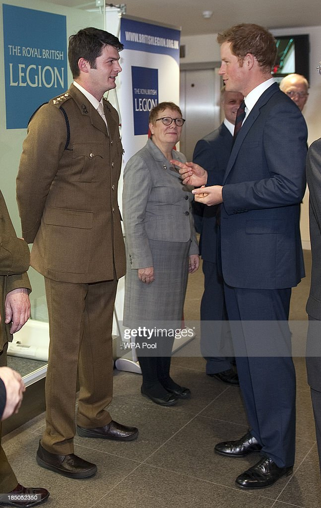 Prince Harry speaks to CPt Dave Henson (L), a bomb disposal captain who lost both of his legs whilst clearing compounds in Afghanistan, during the official opening of the Royal British Legion Centre for Blast Injury Studies at Imperial College London on October 17 in London, England.