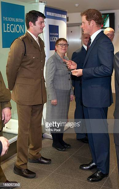 Prince Harry speaks to CPt Dave Henson a bomb disposal captain who lost both of his legs whilst clearing compounds in Afghanistan during the official...