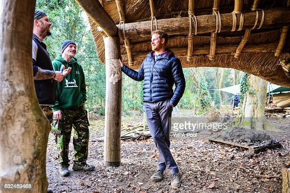 Prince Harry speaks with Mike Day and Eddie Beddoes underneath a mud wood and thatched round house in the woodland area during a visit to a Help For...
