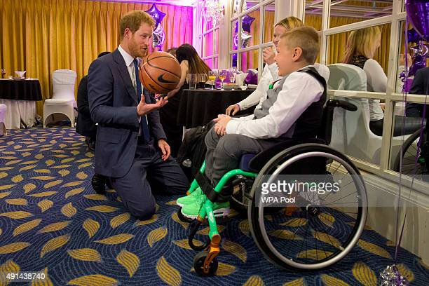 Prince Harry speaks with Toby SweeneyCroft Inspirational Young Person Award winner in the 710 yearsold age group and his mother Rebecca who presented...