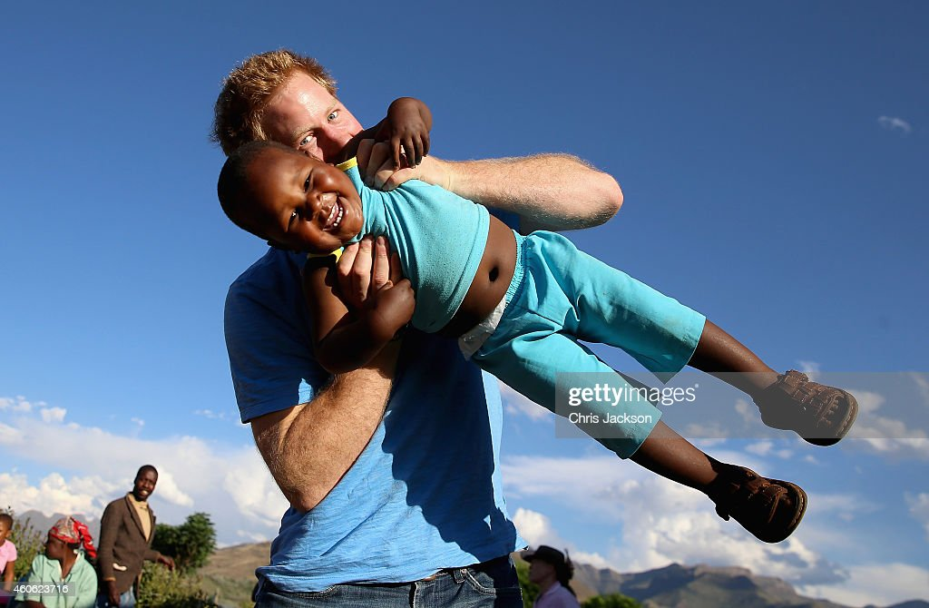 Prince Harry swings young three year old orphan boy called Lerato in this photograph taken with the help of a three year old blind girl called Karabo during a visit to Phelisanong Children's Home on December 6, 2014 in Maseru, Lesotho. Prince Harry was visiting Lesotho to see the work of his charity Sentebale. Sentebale provides healthcare and education to vulnerable children in Lesotho, Southern Africa. Prince Harry said 'Wow, what a welcome we got! There were forty over-energetic children using us as climbing frames, water fights, and a lot of laughs. The boy flying is Lerato, a 3 year old who was abandoned at birth. The photo was taken by 3 year old Karabo who is blind. She heard the clicks, went to the camera and with a little bit of help on direction, shot this great photo.'