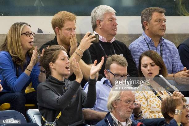 Prince Harry takes a cell phone picture of the wheelchair rugby match between the United States and Denmark at the Invictus Games in Toronto Ontario...