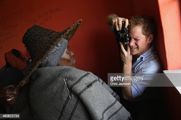 Prince Harry takes a photograph on a Fuji X100s Camera during a visit to a herd boy night school constructed by Sentebale on December 8 2014 in...
