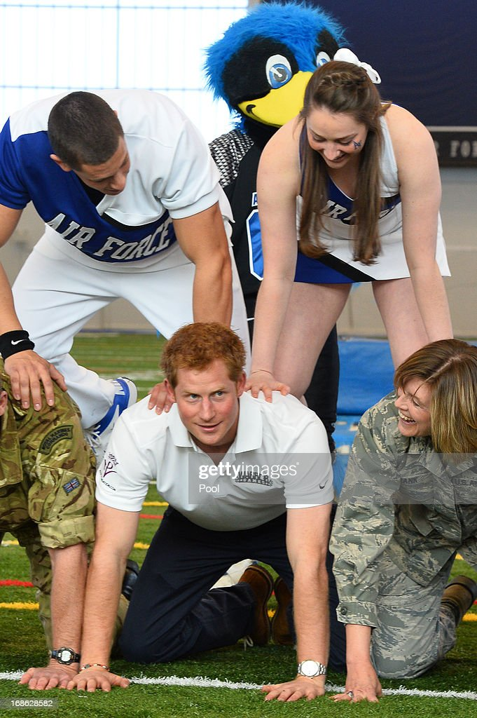 HRH <a gi-track='captionPersonalityLinkClicked' href=/galleries/search?phrase=Prince+Harry&family=editorial&specificpeople=178173 ng-click='$event.stopPropagation()'>Prince Harry</a> takes part in a cheerleading display helping to form the bottom of the pyramid at the United States Air Force Academy's football training center during the fourth day of his visit to the United States on May 12, 2013 in Colorado Springs, Colorado. HRH will be undertaking engagements on behalf of charities with which the Prince is closely associated on behalf also of HM Government, with a central theme of supporting injured service personnel from the UK and US forces.