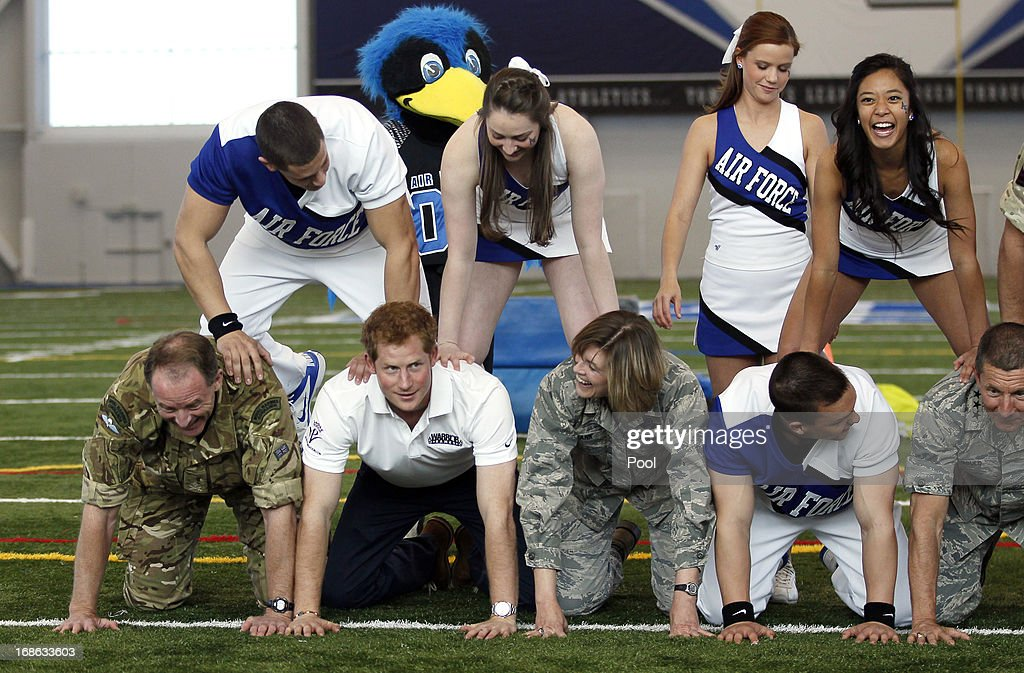 HRH Prince Harry takes part in a cheerleading display helping to form the bottom of the pyramid at the United States Air Force Academy's football training center during the fourth day of his visit to the United States on May 12, 2013 in Colorado Springs, Colorado. HRH will be undertaking engagements on behalf of charities with which the Prince is closely associated on behalf also of HM Government, with a central theme of supporting injured service personnel from the UK and US forces.
