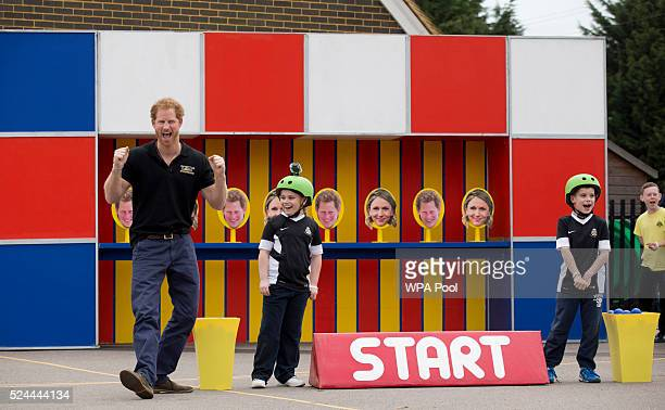 Prince Harry takes part in filming a segment where a photo of him is printed on some of the targets children had to throw balls at for an episode of...