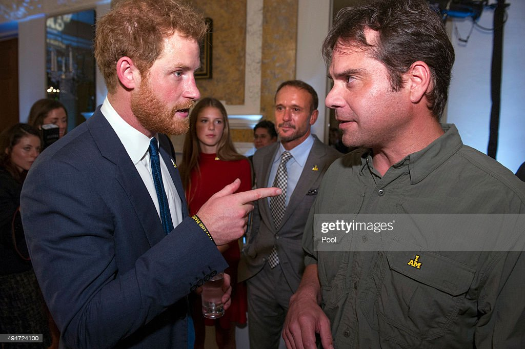 Prince Harry (L) talks with Alejandro Becker (R) of the Tim McGraw foundation, while singer Tim McGraw and his daughter Maggie listen during a reception for the Invictus Games at the British Ambassador's Residence on October 28, 2015 in Washington DC.