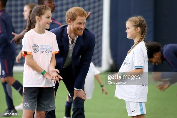Prince Harry talks with children as he visits Manchester City Football Club to drop in on a Coach Core training session on September 4 2017 in...