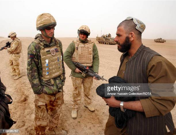 Prince Harry tells a local Afghan man the route around a British Army cordon in the desert on February 21 2008 in Helmand Province Afghanistan