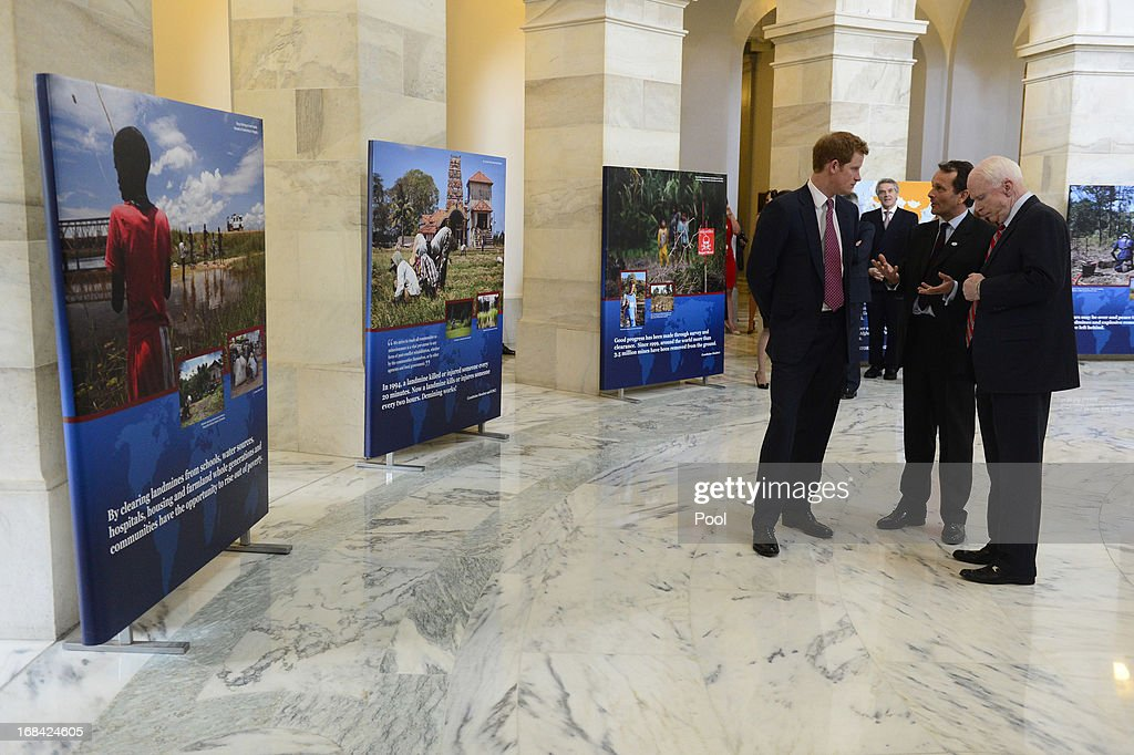 Prince Harry (L) tours a HALO Trust photo exhibit on landmines and unexploded ordinances, with Republican Senator from Arizona John McCain (R) and Halo Trust Director Guy Willoughby (2-R), on Capitol Hill on May 9, 2013 in Washington, DC. HRH will be undertaking engagements on behalf of charities with which the Prince is closely associated on behalf also of HM Government, with a central theme of supporting injured service personnel from the UK and US forces.