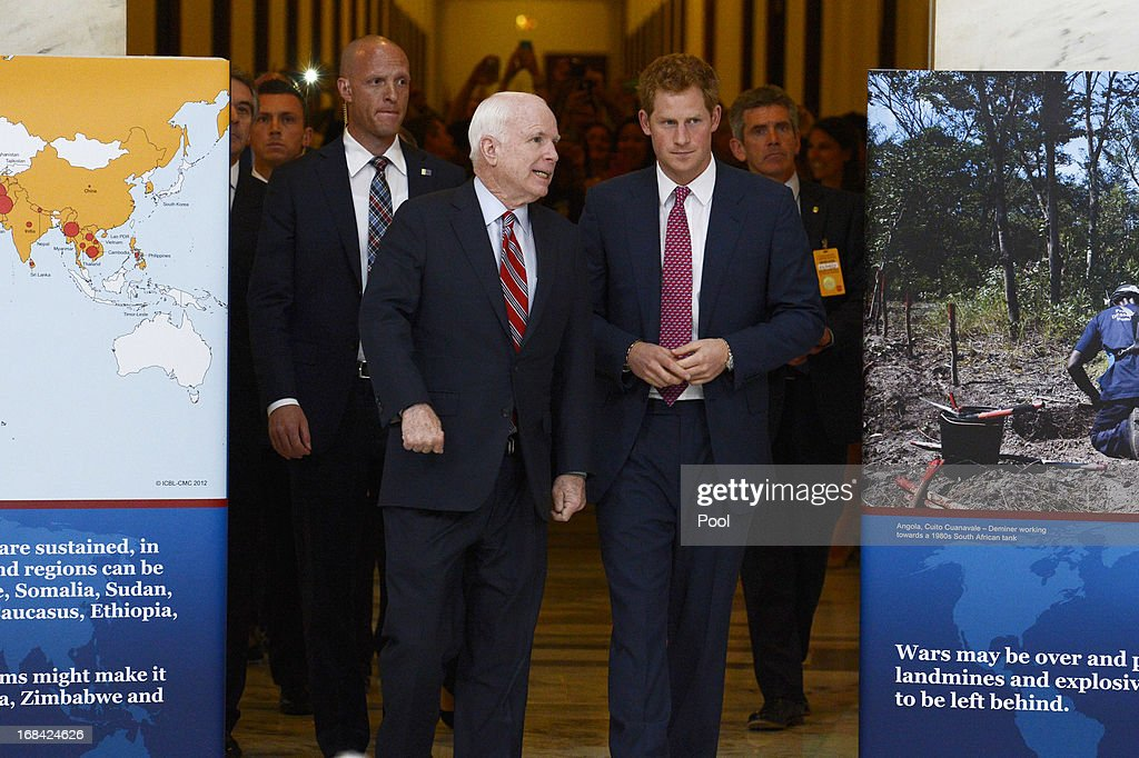 Prince Harry (R) tours a HALO Trust photo exhibit on landmines and unexploded ordinances, with Republican Senator from Arizona John McCain (L), on Capitol Hill on May 9, 2013 in Washington, DC. HRH will be undertaking engagements on behalf of charities with which the Prince is closely associated on behalf also of HM Government, with a central theme of supporting injured service personnel from the UK and US forces.