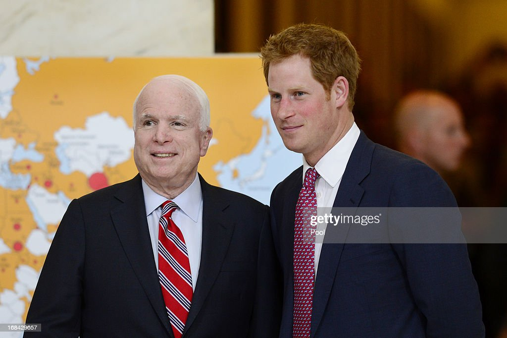 Prince Harry (R) tours a HALO Trust photo exhibit on landmines and unexploded ordinances, with Republican Senator from Arizona <a gi-track='captionPersonalityLinkClicked' href=/galleries/search?phrase=John+McCain&family=editorial&specificpeople=125177 ng-click='$event.stopPropagation()'>John McCain</a> (L), on Capitol Hill on May 9, 2013 in Washington, DC. HRH will be undertaking engagements on behalf of charities with which the Prince is closely associated on behalf also of HM Government, with a central theme of supporting injured service personnel from the UK and US forces.